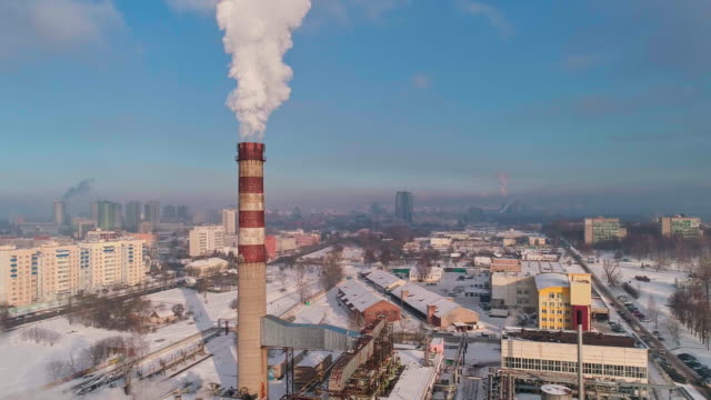 bad ecology. the thermal power plant located in the center of the residential district, throws out smoke from the high pipe, polluting the atmosphere of the city. aerial drone video with orbit camera motion. - centrale termoelettrica video stock e b–roll