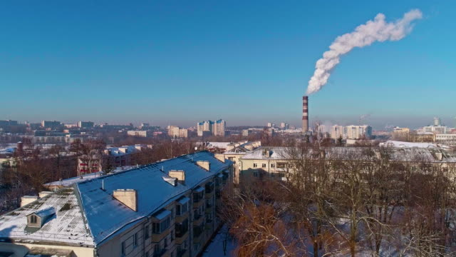 bad ecology. the thermal power plant located in the center of the residential district, throws out smoke from the high pipe, polluting the atmosphere of the city. aerial drone video with descending camera motion. - centrale termoelettrica video stock e b–roll