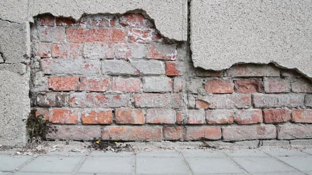 Bad foundation base on old house or building cracked plaster facade wall with brick background