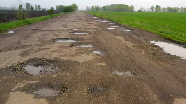 schlechte landstraße mit den vielen grubenlöchern und pfützen nach dem regen - asphalt stock-videos und b-roll-filmmaterial