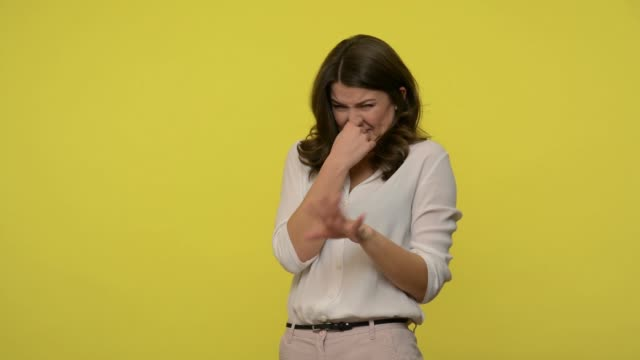 vídeos de stock e filmes b-roll de bad smell! displeased woman with brunette hair in blouse pinching her nose and showing stop gesture - cheiro desagradável