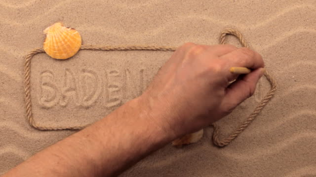 Baden Baden inscription written by hand on the sand, in the pointer made from rope. video