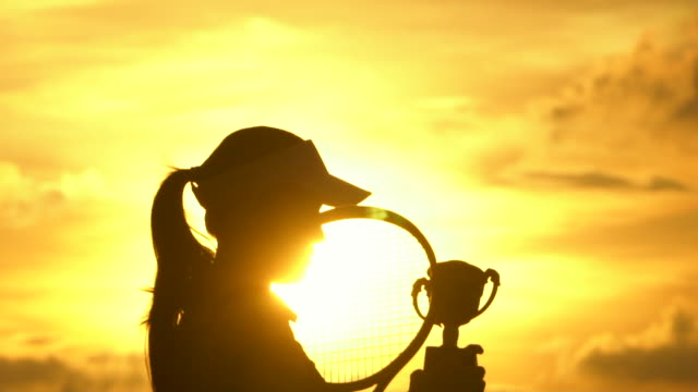 A badminton Player Celebrates winning Game at Sunset silhouette