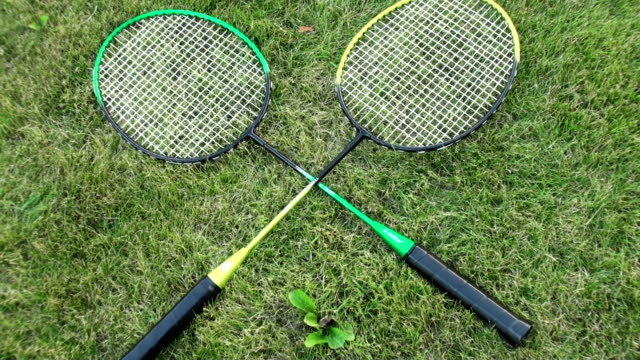 Badminton rackets on green summer grass. male and female hand takes the racket video