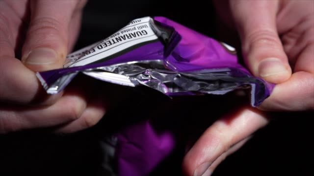 bag of tortilla cheese chips opened slow motion This slow motion video shows anonymous hands opening a bag of delicious tortilla cheese chips. potato chip stock videos & royalty-free footage