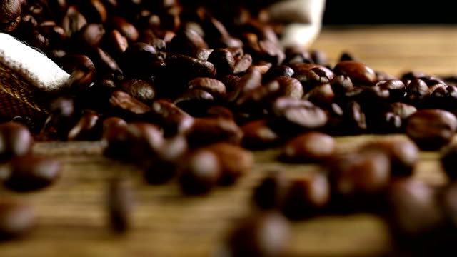 Bag with coffee beans falls and coffee beans are scattered Bag with coffee beans falls and coffee beans are scattered hot pockets stock videos & royalty-free footage