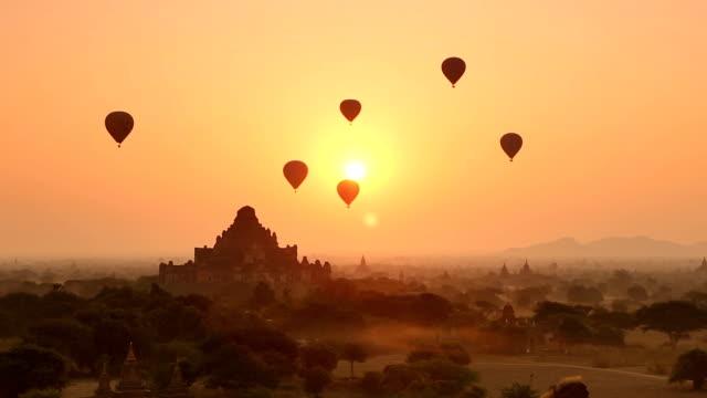 Bagan Sunrise Scene Hot air balloons floating over ancient temples during sunrise in Bagan, Myanmar. myanmar stock videos & royalty-free footage