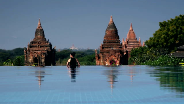 Bagan Temple Pool View Beautiful girl relaxing in an infinity pool with view of the ancient temples in Bagan, Myanmar. bagan stock videos & royalty-free footage