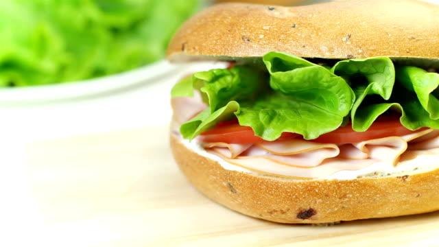 bagel smörgås med färskost, korv, tomat och sallad blad, närbild, dolly skott - cheese sandwich bildbanksvideor och videomaterial från bakom kulisserna