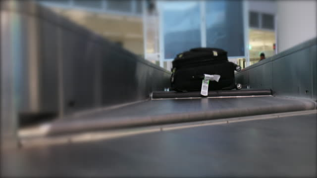 stockvideo's en b-roll-footage met bagage claim in internationale luchthaven. mensen picking up koffer en tassen van conveyor belt 4k - airport pickup
