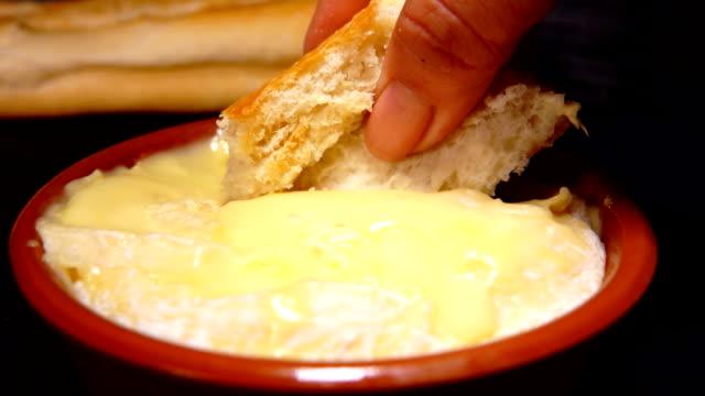 baguette dunk in preheated saint-felicien cheese - cucina francese video stock e b–roll