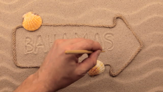 Bahamas inscription written by hand on the sand, in the pointer made from rope. video