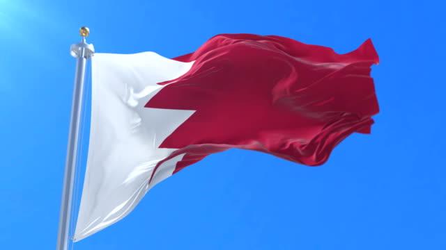 Bahrain flag waving at wind in slow with blue sky, loop video
