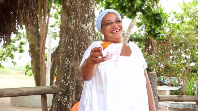vídeos de stock, filmes e b-roll de baiana servindo um alimento típico no brasil chamado acaraje - brasileiro pardo