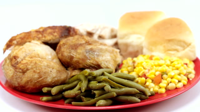 Baked chicken plated with vegetables and rolls. Left rotating. Wide Shot. video