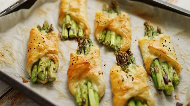 asparagi verdi al forno in pasta sfoglia cosparsi di semi di sesamo. posto su una carta da forno bianca - antipasto video stock e b–roll