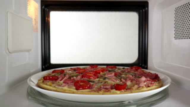 Baked mushroom ham pizza heating in microwave oven inside view video