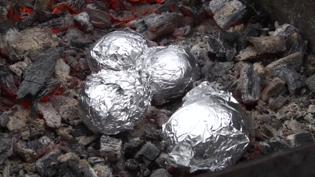 baked potatoes wrapped with aluminum foil roasting in a bonfire. close up of potatoes cooked on barbecue. video filming with hands without stabilization. - aluminum foil stock videos & royalty-free footage