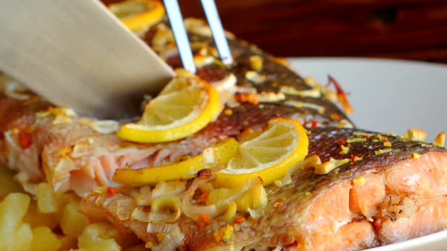 Baked salmon with pineapple and slices of lemon on a plate on a Baked salmon with pineapple and slices of lemon on a plate on a wooden background. cooked stock videos & royalty-free footage