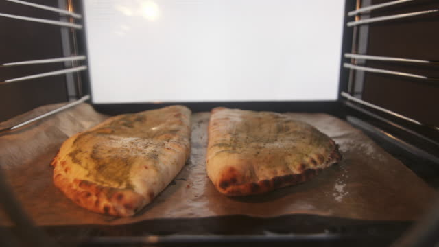 Baked traditional italian pizza calzone in the oven timelapse Baked traditional italian pizza calzone in the oven timelapse. Frozen stuffed pizza calzone on a baking sheet cooking inside modern electric cooker. hot pockets stock videos & royalty-free footage