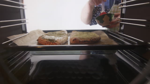 Baked traditional italian pizza calzone in the oven Baked traditional italian pizza calzone in the oven. Woman cooking frozen stuffed pizza pockets with electric oven. View from inside of cooker. hot pockets stock videos & royalty-free footage