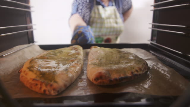 Baked traditional italian pizza calzone in the oven Baked traditional italian pizza calzone in the oven. Woman placing frozen stuffed pizza pockets on a baking sheet into the oven. View from inside of cooker hot pockets stock videos & royalty-free footage