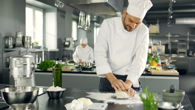 vidéos et rushes de boulanger chef du célèbre restaurant pétrit la pâte dans une cuisine moderne de regard. - boulanger