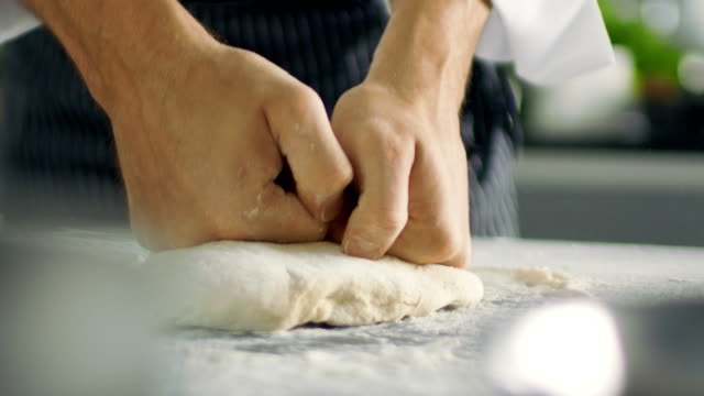 baker chef of famous restaurant kneads the dough in a modern looking kitchen. - impasto video stock e b–roll