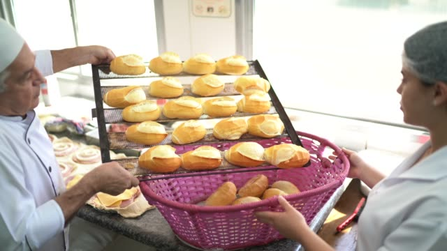 Baker filling a basket with fresh bread