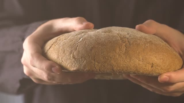 baker hands breaking homemade bread. close up view - attività del fine settimana video stock e b–roll