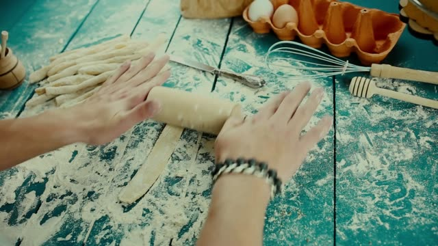 Baker hands preparing fresh dough with rolling pin on kitchen table.