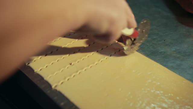 Baker is using pastry wheel for cutting dough into pieces.