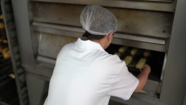 Baker placing bread in the oven