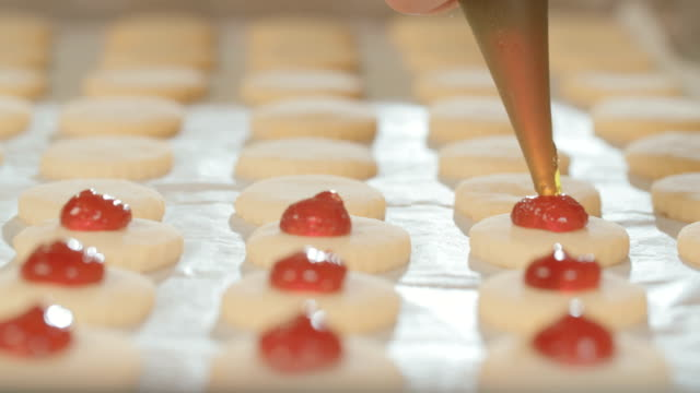 Baker preparing butter cookies with strawberry jam and powdered sugar Baker preparing butter cookies with strawberry jam and sprinkling powdered sugar cookie cutter stock videos & royalty-free footage