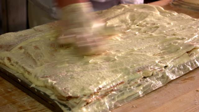 baker förbereder napoleon tårta. - vaniljsås bildbanksvideor och videomaterial från bakom kulisserna
