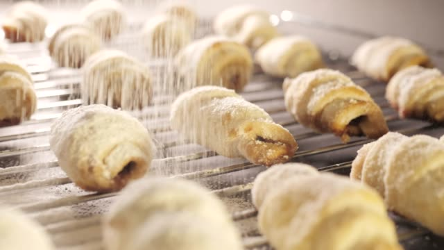 Baker sprinkling sugar powder over butter cookies. Lush Fresh croissants with powdered flour on top video