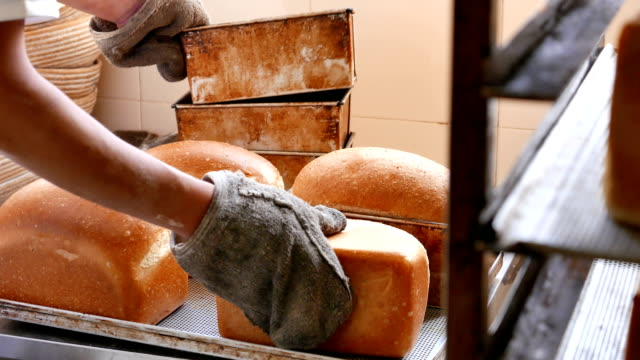 Baker turning out freshly baked bread video
