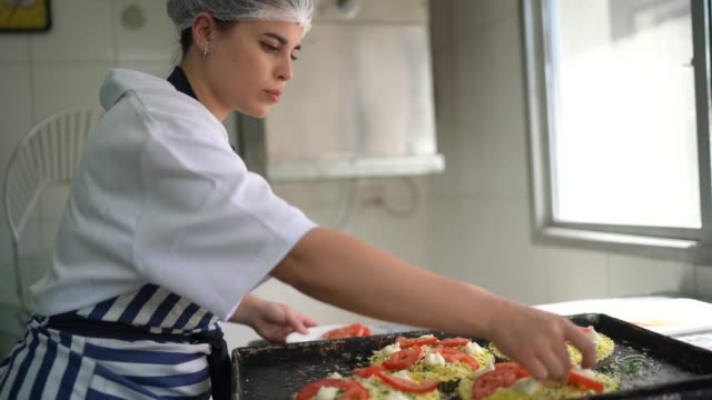 Baker woman preparing mini pizzas at commercial kitchen
