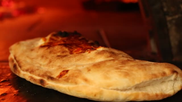 A baker's calzone pizza with a traditional Mediterranean wood-burning oven (wood-fired oven),Italian food-calzone stuffed.Close up