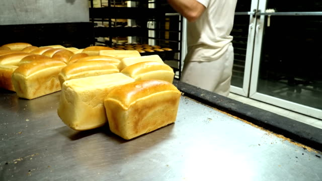 bakers gets bread from the baking dish - formare pane video stock e b–roll