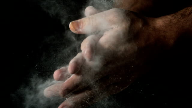 Bakers hands clapping flour off on black background Bakers hands clapping flour off on black background in slow motion flour stock videos & royalty-free footage