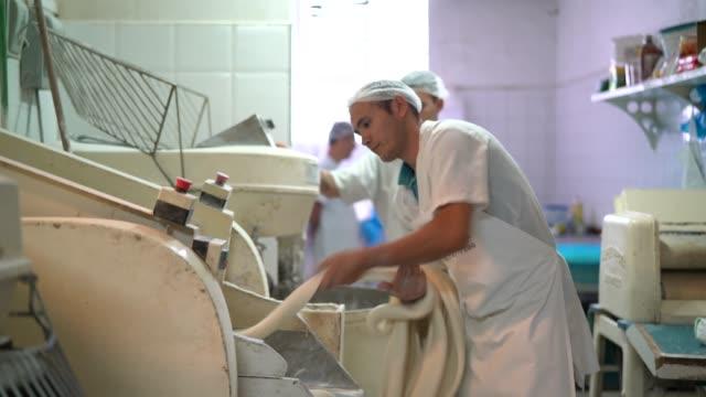 vidéos et rushes de boulangers travaillent dans la cuisine professionnelle à la boulangerie - boulanger