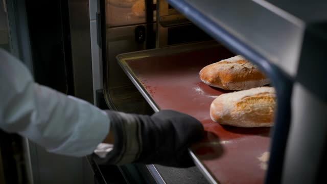 bäckerei, auf dessen hand die besondere dicke handschuhe, zieht der die fettpfanne mit frisch gebackenem brot und einem kleinen in der mitte schnitt - selbstgemacht stock-videos und b-roll-filmmaterial