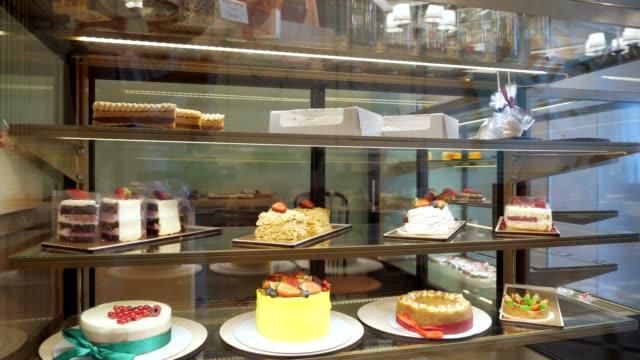 vidéos et rushes de vitrine de boulangerie avec des gâteaux et des pâtisseries sur des étagères en verre. - pâtisseries et feuilletés