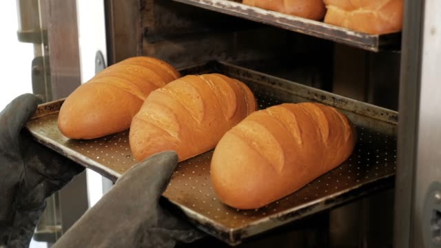 baking bread in the oven. kitchen worker takes out the bread from the oven in bakery. - pane forno video stock e b–roll