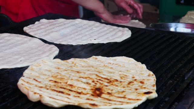 Baking dough on the grill - Woman hand putting buns on barbecue grill. Grilling pizza bread.
