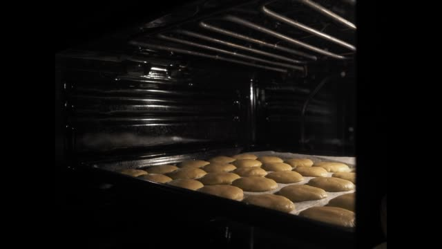 Baking homemade cookies in the oven. Shortbread cookies increase in size during the baking process.
