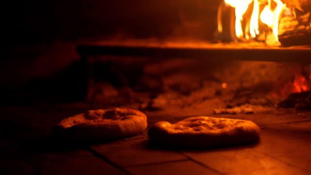 baking pita bread in brick oven - chleb pita filmów i materiałów b-roll