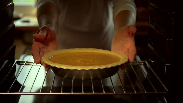 vídeos de stock e filmes b-roll de baking pumpkin pie for the holidays in the oven - 4k video - christmas cooking