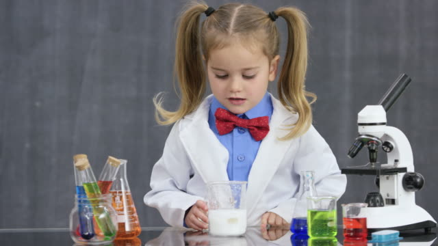 Baking Soda & Vinegar Experiment A preschool aged girl dressed in a bowtie and lab coat stands behind a table with scientific instruments - flasks, beakers, and a microscope.  genius stock videos & royalty-free footage